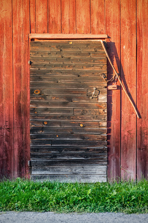 Old weathered black barn door with locks and shingles on red wooden wall photo