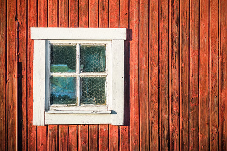 古い赤い木製の納屋の壁、スウェーデンで正方形の白いウィンドウのクローズ アップ 写真素材