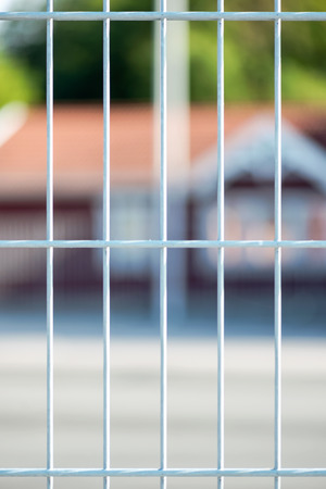 Closeup of a metal fence with blurred red house in background photo