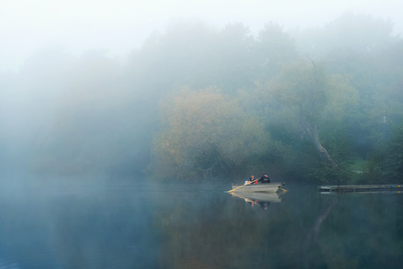 Stockholm, Sweden - Sep 19, 2014: Two men inspecting lake Trekanten with a rowing boat during a early misty morning in Stockholm, Sweden