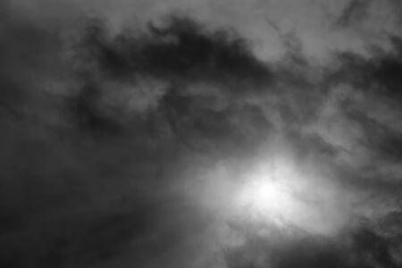 Dark clouds in black and white with sun shining through photo