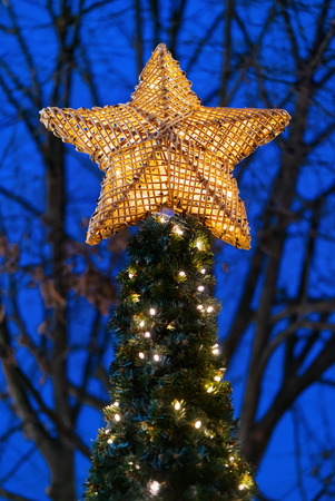 star in bright yellow light in top of a christmas tree outside during evening stock