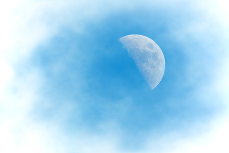Half Moon Phase during day on a cloudy blue sky - manipulated clouds