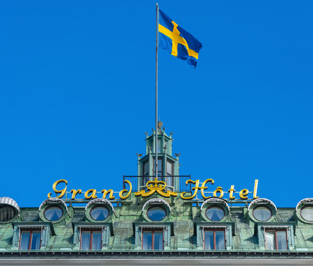 laureates: STOCKHOLM, SWEDEN - MAR 31: Grand Hotel sign with the swedish flag on top of the roof, March 31, 2015 in Stockholm, Sweden. Since 1901, the Nobel Prize laureates and their families have traditionally been guests at the hotel
