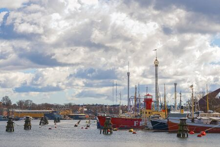 embarked: STOCKHOLM, SWEDEN - MAR 31: Skeppsholmen with boats embarked with Grona Lund in background during a sunny cloudy day, March 31, 2015 in Stockholm, Sweden.
