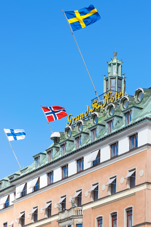 STOCKHOLM, SWEDEN - MAR 31: Facade of the Grand Hotel in Stockholm with flags on blue sky, March 31, 2015 in Stockholm, Sweden. Massive statue of August Strindberg by Carl Eldh, from 1942.