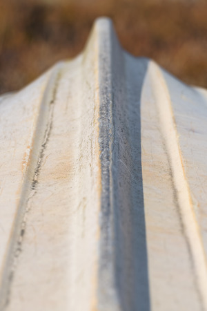 keel: Small boat upside down, used white keel with scratches, detailed short depth of field
