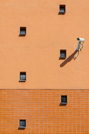 Surveillance camera on orange wall with small windows photo