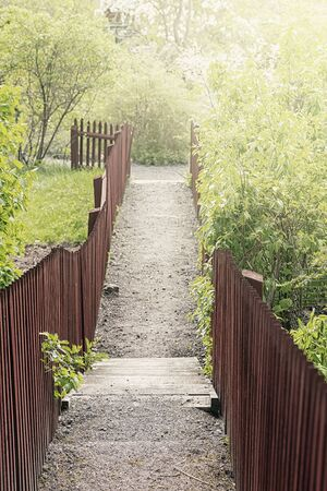 Narrow gravel footpath between two red fences, Sweden. Filters applied
