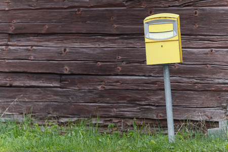 Traditional yellow postbox in front og a wooden wall, vintage style. Sweden Stock Photo