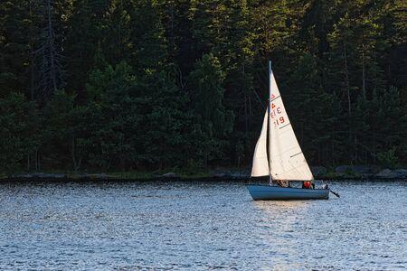 sailingboat: GRISSLEHAMN, SWEDEN - JULY 24, 2015: Small sailboat against a dark green background suring afternoon.
