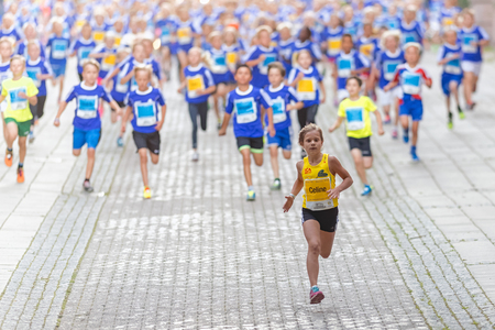 lilla: STOCKHOLM, SWEDEN - AUGUST 15, 2015: Girl in front of a big group of runners at Lilla Midnattsloppet for aged 9. The track is 1775 meters and the runners are aged 8-15 years. Editorial