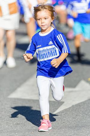 coureur: STOCKHOLM, SWEDEN - 15 août 2015: Jeune fille avec un style gracieux au Minimil pour les plus jeunes coureurs à Midnattsloppet. La piste est de 300 mètres et les coureurs sont âgés de 2-8 ans.
