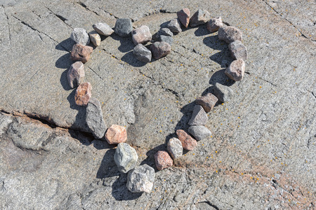 Stones in a heart shaped love sign on granite rock bakground