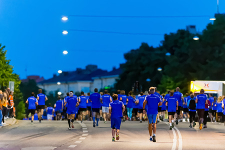 after midnight: STOCKHOLM, SWEDEN - AUGUST 15, 2015: Back of runners after the start at Midnattsloppet or the Midnight run. The track is 10 km and goes thru the streets of Stockholm. Editorial
