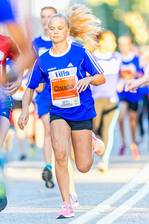 lilla: STOCKHOLM, SWEDEN - AUGUST 15, 2015: Blonde girl running just after the start at Lilla Midnattsloppet for aged 14. The track is 1775 meters and the runners are aged 8-15 years.