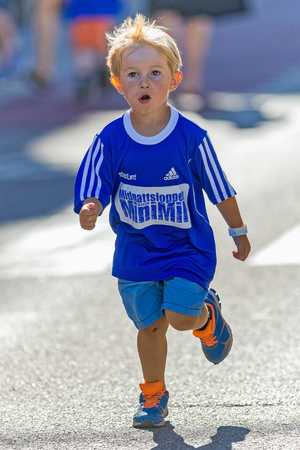 meters: STOCKHOLM, SWEDEN - AUGUST 15, 2015: Young boy with big blue shirt at the final 50 meters at the Minimil for the youngest runners at Midnattsloppet. The track is 300 meters and the runners are aged 2-8 years.