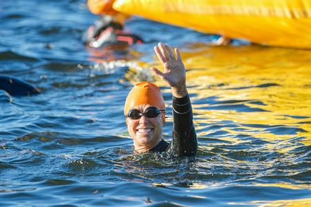 STOCKHOLM - AUG 23, 2015: Happy woman amateur triathlete in closeup waving at Womens ITU World Triathlon event.