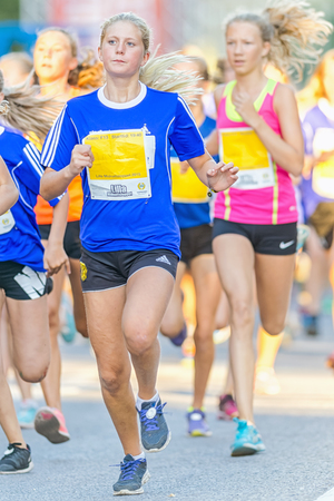 13 15 years: STOCKHOLM, SWEDEN - AUGUST 15, 2015: Girl with great running steps at Lilla Midnattsloppet for runners aged 13. The track is 1775 meters and the runners are aged 8-15 years.