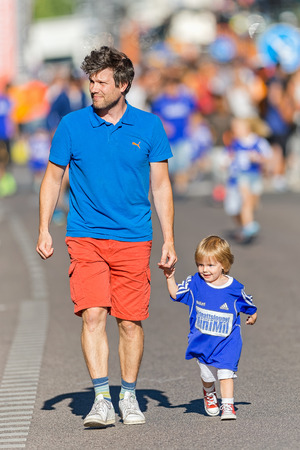 pace: STOCKHOLM, SWEDEN - AUGUST 15, 2015: Dad keeping pace with his kid at the Minimil for the youngest runners at Midnattsloppet. The track is 300 meters and the runners are aged 2-8 years.