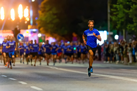 after midnight: STOCKHOLM, SWEDEN - AUGUST 15, 2015: Runner taking the lead just after the start at Midnattsloppet or the Midnight run. The track is 10 km and goes thru the streets of Stockholm.