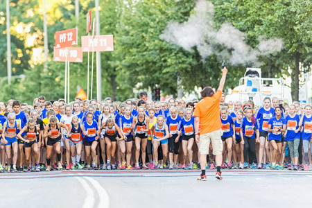 14 15 years: STOCKHOLM, SWEDEN - AUGUST 15, 2015: The starter shoots the pistol and the field is on the way at Lilla Midnattsloppet for aged 14. The track is 1775 meters and the runners are aged 8-15 years.