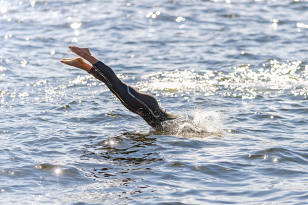 triathlete: STOCKHOLM - AUG 22, 2015: Woman triathlete diving into the water at the Womens ITU World Triathlon series event in Stockholm.