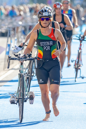 triathlete: STOCKHOLM - AUG 23, 2015: Female triathlete running with bike and shoes in the transition area the ITU World Triathlon event in Stockholm.
