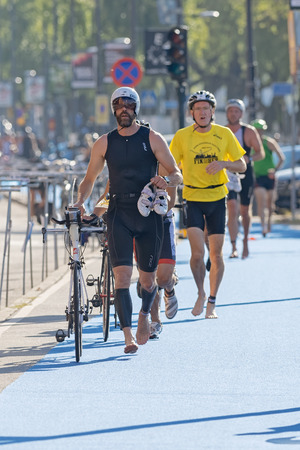 triathlon: STOCKHOLM - AUG 23, 2015: Male triathletes running with bike and shoes in the transition area the ITU World Triathlon event in Stockholm. Editorial