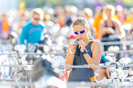 triathlete: STOCKHOLM - AUG 23, 2015: Female triathlete preparing and fixing with her goggles before the ITU World Triathlon event in Stockholm.