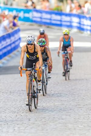 ger: STOCKHOLM - AUG 22, 2015: Sophia Saller (GER) leading a group down on the cobblestones at the Womens ITU World Triathlon series event in Stockholm.