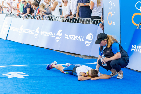STOCKHOLM - AUG 22, 2015: Alice Betto (ITA) lies in the goal area and is very tired at the Womens ITU World Triathlon series event in Stockholm. Editorial