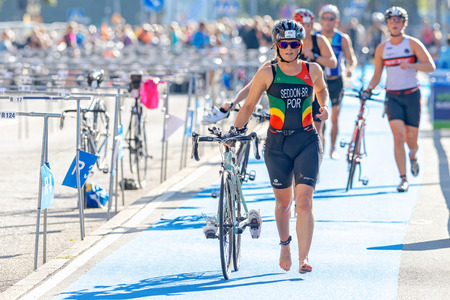 transition: STOCKHOLM - AUG 23, 2015: Female triathlete running with bike and shoes in the transition area the ITU World Triathlon event in Stockholm.