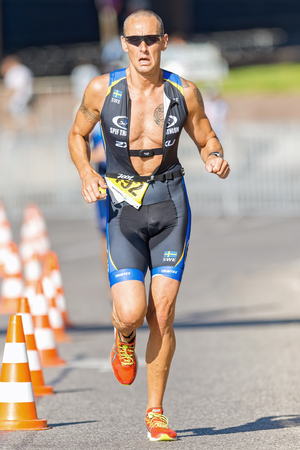 triathlete: STOCKHOLM - AUG 23, 2015: Closeup of a triathlete running in the sunny weather at ITU World Triathlon event in Stockholm.