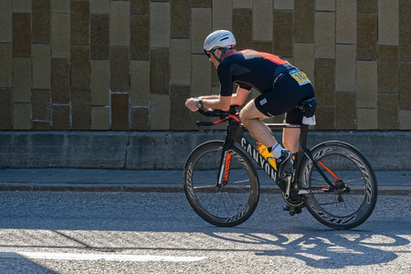 speedy: STOCKHOLM - AUG 23, 2015: Triathlete cycling with a speedy bike in partial sunlight at the ITU World Triathlon event in Stockholm.