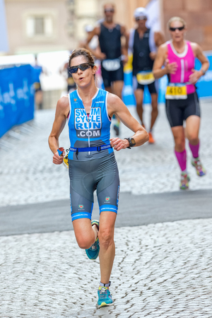 triathlete: STOCKHOLM - AUG 23, 2015: Woman triathlete running down the cobblestones in the old town at the ITU World Triathlon event in Stockholm. Editorial