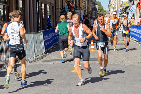 STOCKHOLM - AUG 23, 2015: Triathletes running at the cobblestones in the old town at the ITU World Triathlon event in Stockholm. Stock Photo - 45700316