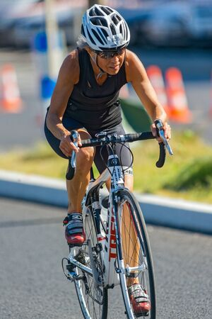 triathlete: STOCKHOLM - AUG 23, 2015: Determined woman triathlete on the bike at the ITU World Triathlon event in Stockholm.