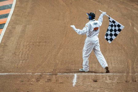 STOCKHOLM - SEPT 26, 2015: Referee with a chequered flag at the finish line at TEGERA Stockholm FIM Speedway Grand Prix at Friends Arena in Stockholm. Redakční
