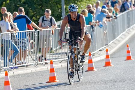 braking: STOCKHOLM - AUG 23, 2015: Triathlete braking before a curve at the ITU World Triathlon event in Stockholm. Editorial
