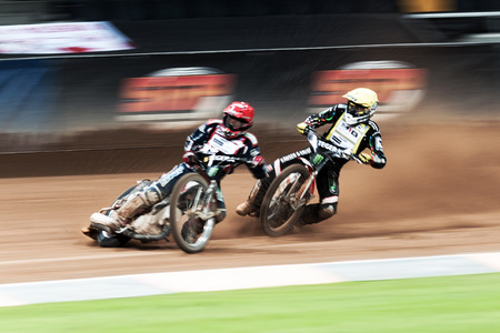 STOCKHOLM - SEPT 26, 2015: Two speedway racers in action with motion blur at the TEGERA Stockholm FIM Speedway Grand Prix at Friends Arena in Stockholm.