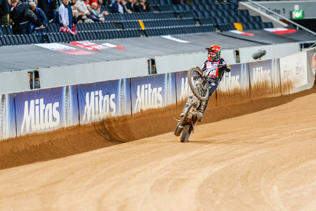 wheelie: STOCKHOLM - SEPT 26, 2015: Tai Woffinden doing a wheelie after his victory at the TEGERA Stockholm FIM Speedway Grand Prix at Friends Arena in Stockholm. Editorial