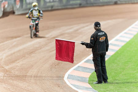 racer flag: STOCKHOLM - SEPT 26, 2015: Referee stopping the race with a red warning flag at TEGERA Stockholm FIM Speedway Grand Prix at Friends Arena in Stockholm.
