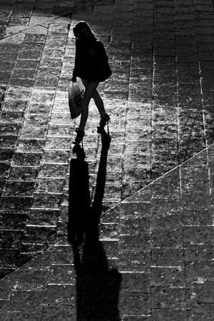 people shadow: Silhouette of a female shopper with long black shadows. Black and white Stock Photo