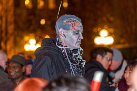 scaring: STOCKHOLM, SWEDEN - OCT 31, 2015: Man in zombie look scaring people at Halloween parade Shockholm in Kungstradgarden