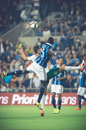 rivals: STOCKHOLM, SWEDEN - AUG 24, 2015: Colley and Haglund jumping for the ball at the soccer game between the rivals Djurgarden and Hammarby at Tele2 arena.