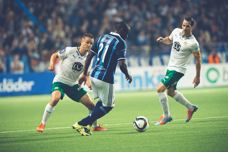 dribbling: STOCKHOLM, SWEDEN - AUG 24, 2015: Mushekwi dribbling the ball at the soccer game between the rivals Djurgarden and Hammarby at Tele2 arena.