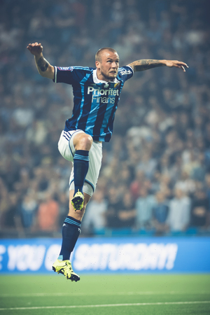 rivals: STOCKHOLM, SWEDEN - AUG 24, 2015: Alexander Faltsetas jumping high at the soccer game between the rivals Djurgarden and Hammarby at Tele2 arena.