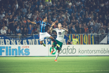 rivals: STOCKHOLM, SWEDEN - AUG 24, 2015: Two players jumping for the ball at the soccer game between the rivals Djurgarden and Hammarby at Tele2 arena.