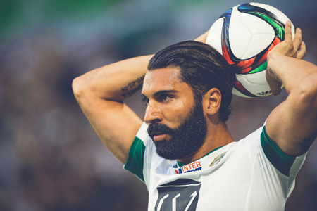 rivals: STOCKHOLM, SWEDEN - AUG 24, 2015: Throw in by Stefan Batan (HIF) at the soccer game between the rivals Djurgarden and Hammarby at Tele2 arena.